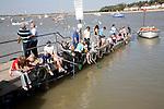 People crabbing from jetty, Felixstowe Ferry, Suffolk, England