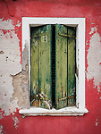 Weathered red wall with window and withered green shutters, the colorful village of Burano, Italy.
