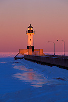 The Duluth Minnesota North Pier Lighthouse in winter at dusk on Lake Superior.