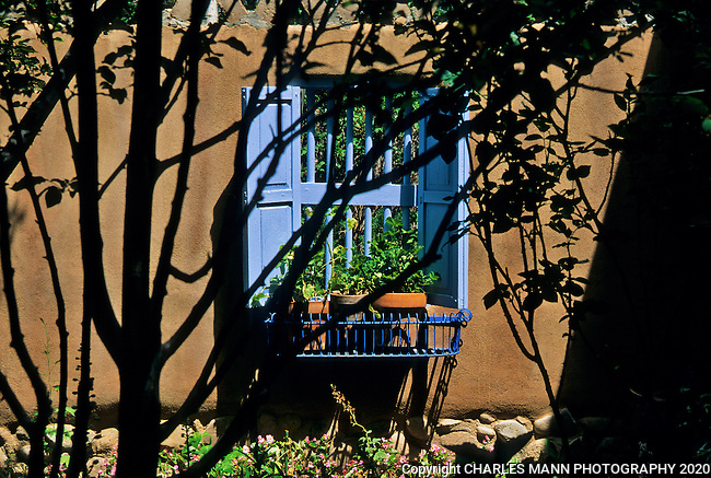 The gardens of Santa Fe,New Mexico, offer a constant suppply of delightful surprises and artful delights. A blue window is at home in a brown adobe wall in another Santa Fe compound.