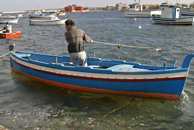 Portopalo, Sicily, Italy, fisherman in boat pulling anchor line.
