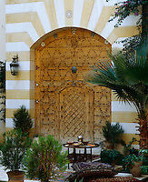A large studded wooden door in a striped marble wall opens onto the courtyard