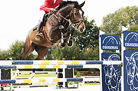 Rider jumping fence at Czech Equestrian masters, held at Equitana Martinice The Czech Republic. Rider wearing red jacket and brown riding boots.Horse in middle of the jump