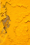 Cracked yellow paint on cement.