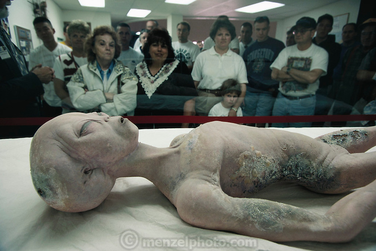 "Replica of an alien body (a movie prop donated to the museum) in the International UFO Museum and Research Center, 114 N. Main St., in downtown Roswell, New Mexico. Museum visitors begin their tour with a short talk by Dennis Balthaser, a ""certified MUFON UFO-ologist"" (Mutual UFO Network). The Roswell incident started on 2 July 1947 when UFO sightings were reported during a thunderstorm. Next morning a rancher, Mac Brazel, discovered strange wreckage in a field. When the impact site was located, a UFO craft and alien bodies were allegedly found. On 8 July 1947, the Roswell Daily Record announced the capture of a flying saucer. (1997)."