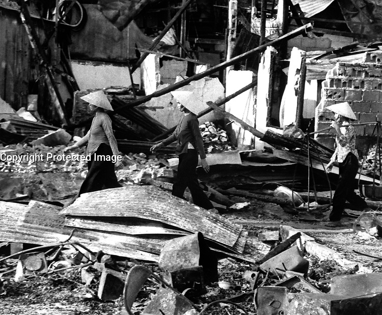 Three Vietnamese women move back into the Cholon area after VC attack that left a two-block area leveled, in hopes of salvaging meager belongings.  Saigon, January 31, 1968.  (USAIA)<br /> NARA FILE #:  306-MVP-5-4<br /> WAR & CONFLICT BOOK #:  421