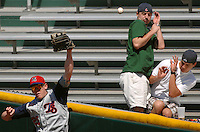 Jacksonville Suns baseball fans Daniel Johnson (center) and his brother Ryan Johnson (right) attempt to shield themselves from the home run baseball hit into the right field bleachers as Tennessee Smokies right fielder #25 Ryan Harvey (left) fails to get his glove on the ball at the Baseball Grounds of Jacksonville in Jacksonville, Fl. (The Florida Times-Union, Rick Wilson)