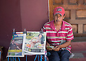 25/02/16 <br /> <br /> A newspaper vendor, wearing an 'I Love Jesus' hat counts money as a large breasted woman is displayed on one of his newspapers in Granada, Nicaragua.<br /> <br /> All Rights Reserved: F Stop Press Ltd. +44(0)1335 418365   +44 (0)7765 242650 www.fstoppress.com