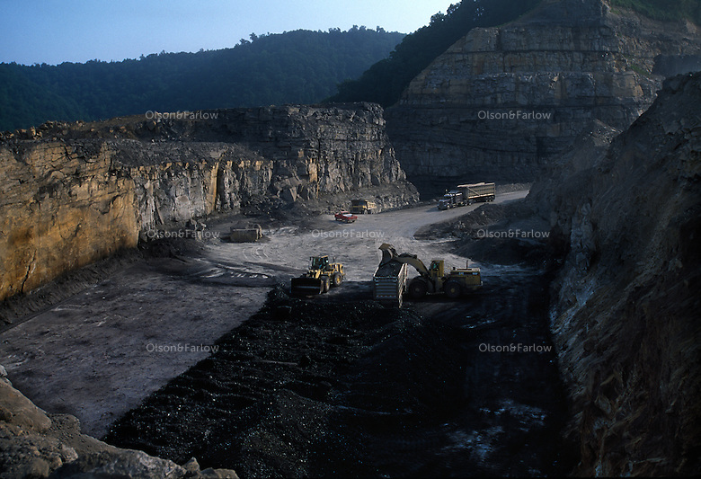 Mountaintop removal mine site. Eauipment moves digs through a coal seam and loads the rock onto trucks. Excess rock is moved to fill in valleys between mountains.