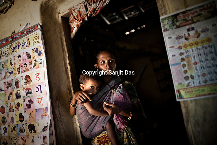 Meena is seen watching television in her house in village Godhari in Chattisgarh, India. Meena is educated and runs a small study centre in the village. Photo: Sanjit Das