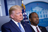 United States President Donald J. Trump, left, and United States Secretary of Housing and Urban Development (HUD) Ben Carson listen during a news conference on the Coronavirus crisis in the Brady Press Briefing Room of the White House in Washington, DC on Saturday, March 21, 2020.  Credit: Stefani Reynolds / Pool via CNP/AdMedia