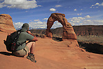 Man viewing Delicate Arch in Arches National Park, Moab, Utah, USA. .  John offers private photo tours in Arches National Park and throughout Utah and Colorado. Year-round.