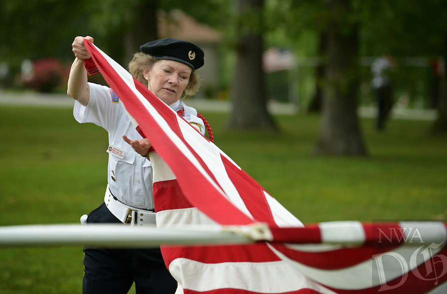 NWA Democrat-Gazette/BEN GOFF @NWABENGOFF<br /> Judith Winchell with the Veterans Honor Guard of Bella Vista helps furl flags on Monday May 30, 2016 before rain begins following the Memorial Day program presented by American Legion Post 341 at Bella Vista Memorial Garden Cemetery.