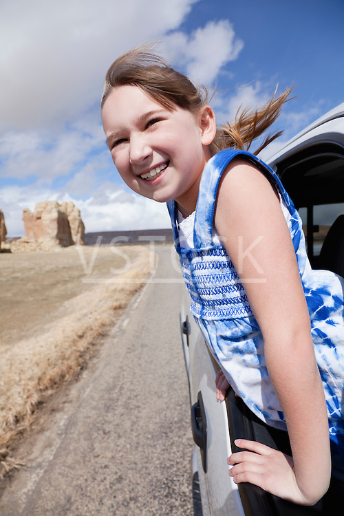 USA, New Mexico, Girl (10-11) leaning out of car window