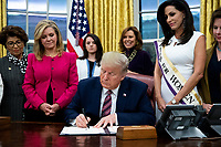 US President Donald J. Trump (C) signs 'the Women's Suffrage Centennial Commemorative Coin Act', beside beside United States Senator Marsha Blackburn (Republican of Tennessee) (L), in the Oval Office of the White House in Washington, DC, USA, 25 November 2019. Trump signed 'H.R. 2423, the Women's Suffrage Centennial Commemorative Coin Act' - a bill directing the US Treasury to mint and issue up to four hundred thousand one-dollar silver coins honoring women that played a role in gathering support for the 19th Amendment.<br /> Credit: Michael Reynolds / Pool via CNP/AdMedia