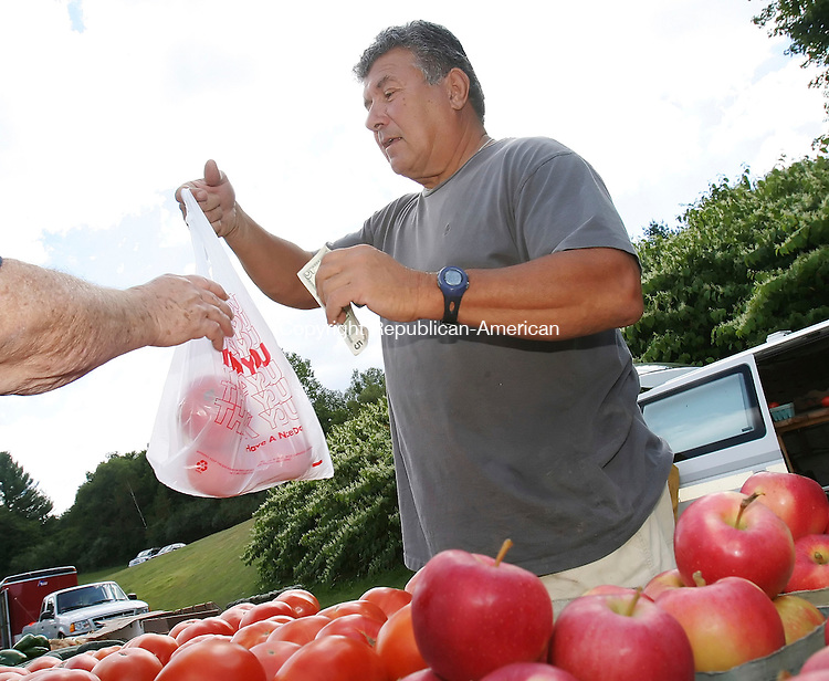 WOODBURY, CT- 10 SEPTEMBER 2005-091005BZ12- Rich Perrotti, of Cheshire, sells tomatoes at the flea market in Woodbury Saturday morning.<br /> Jamison C. Bazinet / Republican-American