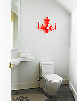 A contemporary wall light in orange plastic that resembles an old-fashioned chandelier on the bathroom wall