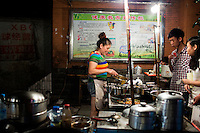 Xie Guang Rong serves tu dou ni (smashed fried potatos mixed with spices) to customers at her food stand outside the B District Middle Gate of Chongqing University in the Shapingba district of Chongqing, China. Xie Guang Rong has run the stand, which serves tu dou ni, jiaozi, and other small snacks, for 11 years. They chose the location directly outside the university gate because it's such a high traffic areas. She said that the stand is popular with students because prices are low and the portions she serves are big. A large helping of tu dou ni, for instance, costs 3RMB. She and her husband rent the stall space from the surrounding community.