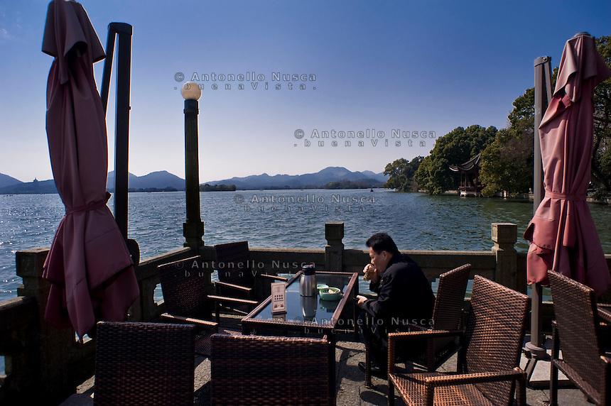 Hangzhou, Cina, 2 marzo, 2015. Un uomo beve il suo te in una terrazza del Lago dell'Ovest.<br /> A man drinking tea in a terrace bar at the West Lake in Hangzhou