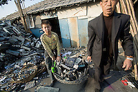 A yong boy and an old man carry a basket of electronic trash in the twon of Nanyang.