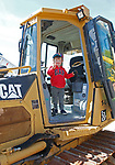 """Torrington, CT 051819MK05 Max Fischer, from Litchfield, mugs for the camera from heavy equipment at the O&G Industries' annual Touch a Truck Family Fun Event at their maintenance facility on Saturday Morning.  Seth Duke, marketing director, said """" With the weather so nice today we will receive over two-thousand attendees and the suggested donations will be donated to Kids Play to help with their continued development.""""  O&G's Jim Zambero, vice president of equipment purchase and maintenance, said that sixty volunteers and twentyfive local vendors helped host the event while members of the Operational Engineer's Union Local #478 directed traffic and managed parking . Michael Kabelka / Republican-American"""