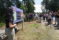 NWA Democrat-Gazette/FLIP PUTTHOFF <br /> NEW TRAIL TO HIKE, BIKE<br /> Suzanne Grobmyer, executive director of the Arkansas Parks and Recreation Foundation, unveils Friday June 7 2019 an information sign during the dedication of a new 17.36-mile trail for hiking and mountain biking at Hobbs State Park-Conservation Area east of Rogers. The trail now open and starts at the visitor center. It is the first of several Monument Trails planned for select Arkansas State Parks, including Devil's Den, Mount Nebo and Pinnacle Mountain state parks. Dedication festivities continue today at 9 a.m. with a ceremonial log cutting in lieu of a ribbon cutting. Guided rides on the new trail start at 10 a.m. Mountain bikes will be available for use at no charge. Monument Trails are at least 10 miles long and have architectural features such as campsites for backpacking and bikepacking. Rogue Trails built the Monument Trail at Hobbs.