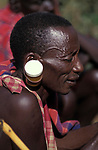 A maasai man at an intiation ceremony  for the Moran coming into manhood.  He has been stretching his ears with a pill container.