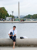 """Stephen Colbert, host of the Comedy Central show """"The Colbert Report"""" puts his sox and shoes back on after working on a bit with United States Representative Jack Kingston (Democrat of Georgia) around the the U.S. Capitol Reflecting Pool in Washington, D.C. on Friday, October 3, 2014.<br /> Credit: Ron Sachs / CNP<br /> (RESTRICTION: NO New York or New Jersey Newspapers or newspapers within a 75 mile radius of New York City)"""