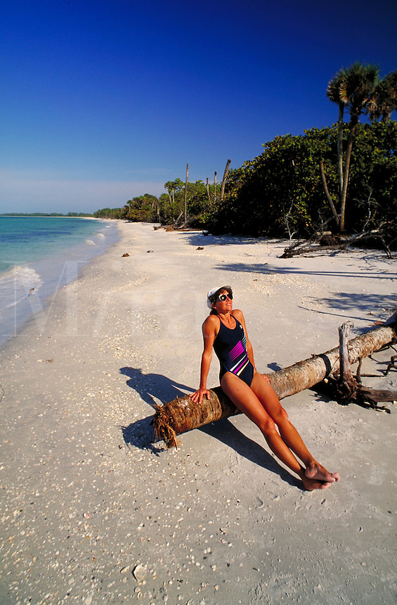 A woman relaxes in the sun on the beach of Cayo Costa State Park, Cayo Costa Island, Florida. Florida, Cayo Costa Island, Cayo Costa State Park, Gulf of Mexico.