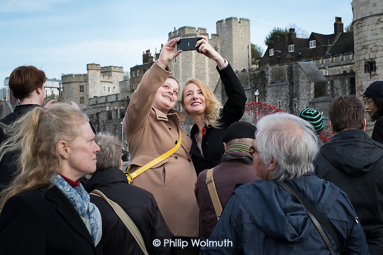 Visitors take smartphone photos and selfies of an art installation of ceramic poppies by Paul Cummins commemorating British and colonial soldiers who died in WW1. Crowds mark Armistice Day at the Tower of London 100 years after the start of the First World War.