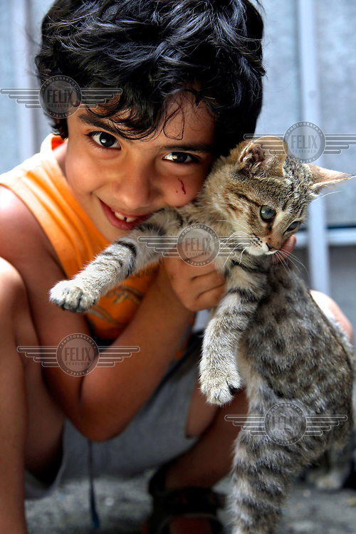 A child plays with a cat in a city suburb.