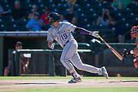 Salt River Rafters third baseman Josh Fuentes (19), of the Colorado Rockies organization, follows through on his swing during an Arizona Fall League game against the Surprise Saguaros on October 9, 2018 at Surprise Stadium in Surprise, Arizona. The Rafters defeated the Saguaros 10-8. (Zachary Lucy/Four Seam Images)
