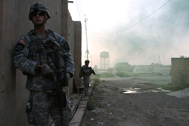 As the sun rises, Staff Sgt.  Brian Piehler, 25, of Spanaway, Wash., and Pfc.  Westin Floeter, 20, of Spokane, Wash., move cautiously from their Stryker armored vehicle into the streets of Baqubah, Iraq, on the first day of a U.S.-led offensive to clear insurgents from the city. The soldiers are with Company C, 1st Battalion, 23rd Infantry Regiment. June 19, 2007. DREW BROWN/STARS AND STRIPES