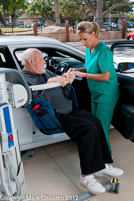 Healthcare professional professional lifts patient into car using KCI medical device