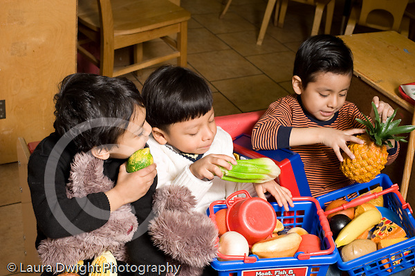 Education Preschool 3-5 year olds pretend play three boys sitting together playing with plastic shopping baskets filled with toy fruits and vegetables horizontal