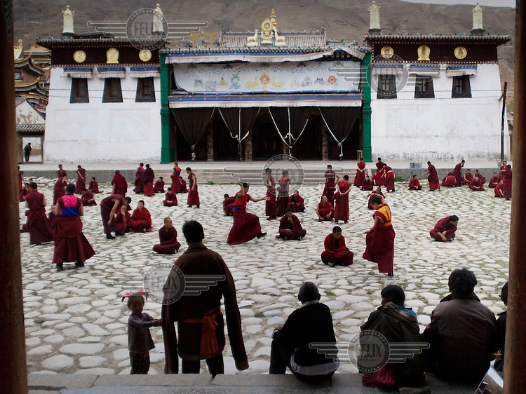 Young Buddhist monks debate in the courtyard of the monastery in Tongren.