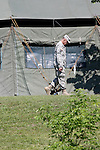 A US Army Soldier walking next to a tent
