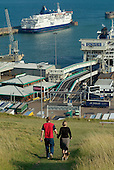 A young couple walk their dogs on the cliffs above the Dover ferry terminal.