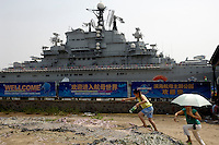 Chinese tourists walk past Soviet aircraft carrier Kiev in a military-theme park in Tianjin, China..19 Aug 2007