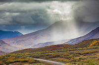 Virga and shaft of light comes through clouds over the Denali Park road, Interior, Alaska.
