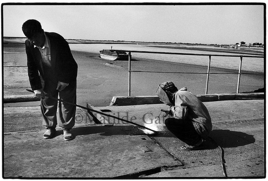 Uzbekistan - Repairing a bridge on the Amu Darya river near Nukus. The bridge is made with parts of stranded boats.