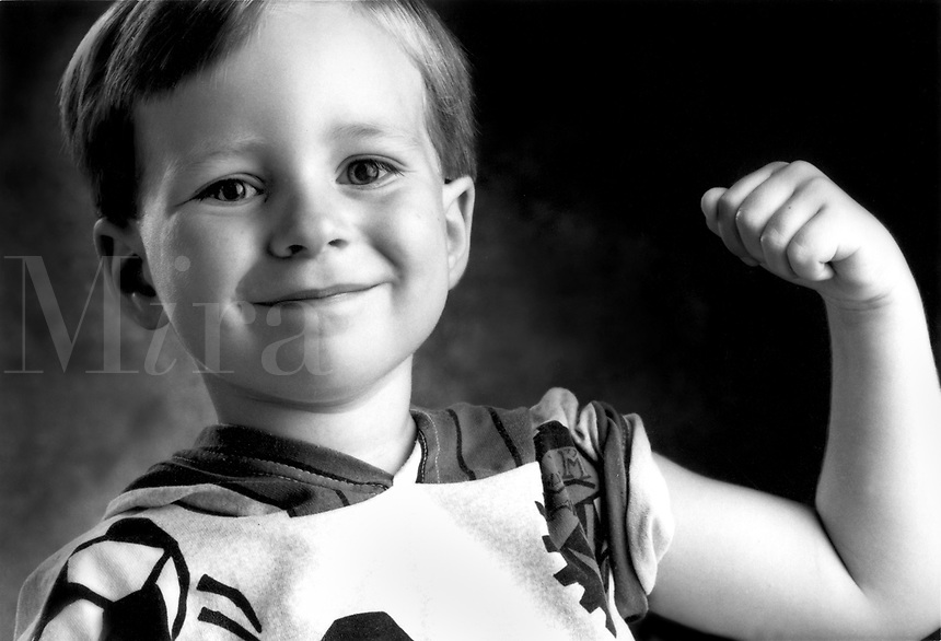 Happy little boy shows bicep muscle.