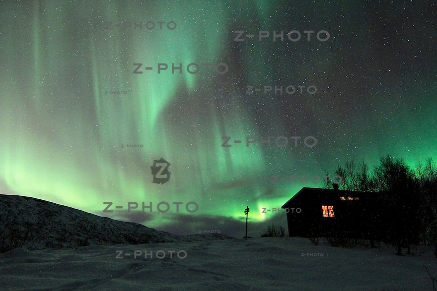 Polarlichter tauchen nachts in der noerdlichen Hemisphaere den Himmel ueber Nordnorwegen in bunte und sich staendig veraendernde Farben. Aurora borealis Waving over North Norway near Troms..Copyright © Zvonimir Pisonic