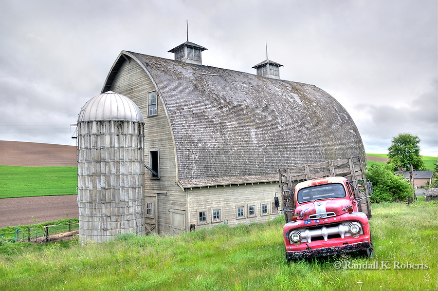 An old red Ford adds a touch of color to this scene of a century-old barn just outside of Colfax, Washington in the Palouse Country.
