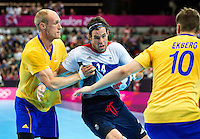 31 JUL 2012 - LONDON, GBR - Steven  Larsson (GBR) of Great Britain (centre, in white, blue and red) looks for a way through Sweden's defence during the men's London 2012 Olympic Games Preliminary round match at The Copper Box in the Olympic Park, in Stratford, London, Great Britain (PHOTO (C) 2012 NIGEL FARROW)