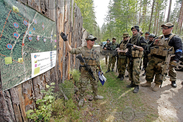 "Players from team SOB (Specia Operations Battalion) hold a breif before the battle. <br /> <br /> Airsoft players fight during the mock war ""Ghost Zone"". The game attracted around 140 players from all over Norway, and is the biggest such event in the country. Dressed in full military gear, complete with replica weapons, players from the two teams Goyo and SOB fought each other to control territory, drugs and money. The guns, softguns, weigh and feel like real weapons but only shoot little plastc pellets. All players wear protective glasses for their eyes, but the pellets are otherwise not considered dangerous."