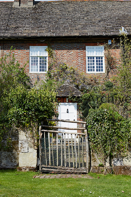 A rustic wooden gate opens onto a pathway leading to the front door of a 1600s house.