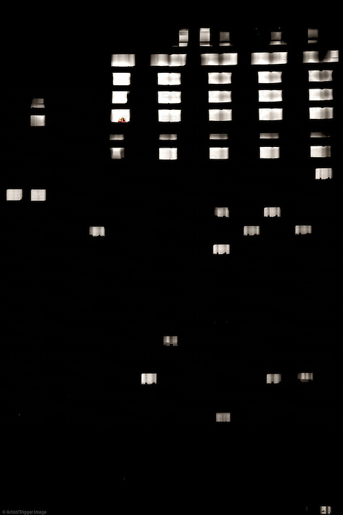The lit by interior light window of a skyscraper in the dark.