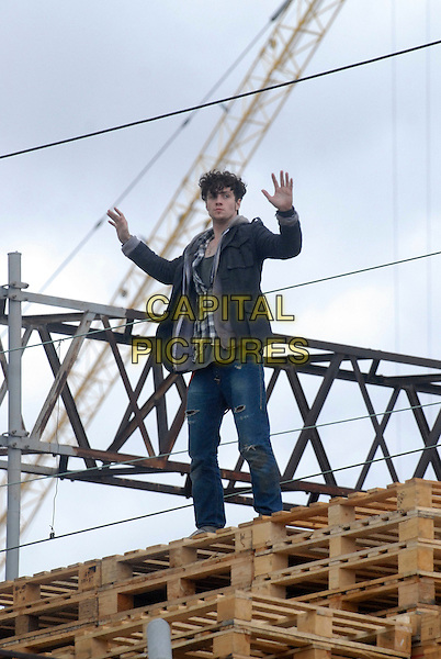 "AARON JOHNSON.Filming on the set of ""Chatroom"", the new Hideo Nakata film, Camden Horse Market, London, England..July 29th, 2009.acting full length jeans denim black jacket gun pallet arms outstretched balance balancing .CAP/IA.©Ian Allis/Capital Pictures."