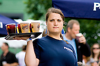 Strong armed waitress delivering a tray of beer and other beverages. Grand Old Day Street Fair St Paul Minnesota USA